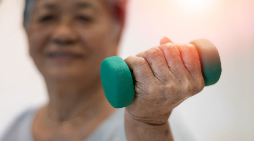 Senior elderly woman hand holding dumbbell in physical therapy session